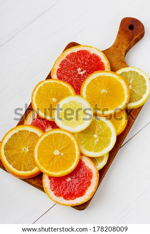 Citrus fruits slices on a wooden board on a white background