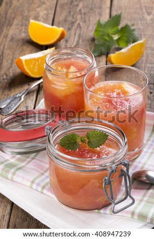 Citrus jelly in a glass jar. Homemade grapefruit orange gelatin dessert. Healthy low fat and low calorie meal. - stock photo