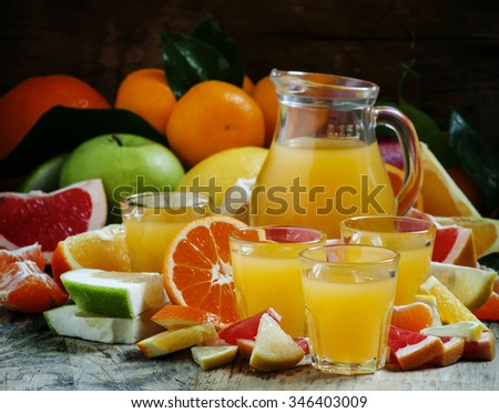 Citrus juice from oranges, tangerines, grapefruits, lemons, apples, pomelo in the glasses and the pitcher on the old wooden background, selective focus - stock photo