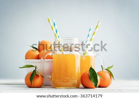Citrus juice in jar with handle and fresh mandarin orange on blue background - stock photo