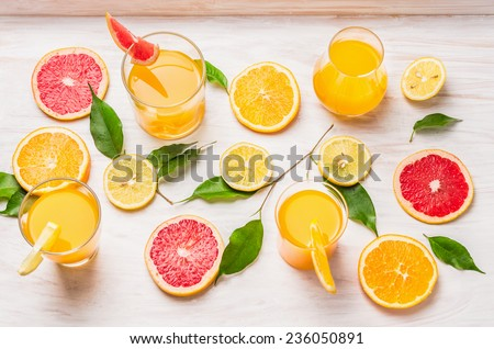 Citrus juices in glass and a slice of orange , grapefruit and lemon on a white wooden background , top view - stock photo