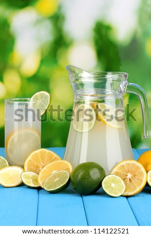 Citrus lemonade in pitcher and glass of citrus around on natural wooden table on blue background