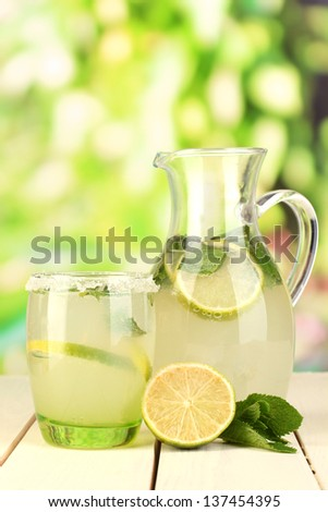 Citrus lemonade in pitcher and glass on wooden table on natural background - stock photo