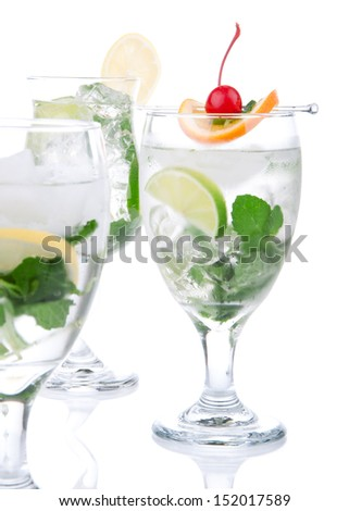 Citrus Mojito cocktails with light rum, vodka, gin, lime, spring of mint, simple soda, orange, maraschino cherry and syrup in cocktail glasses isolated on a white background
