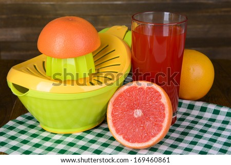 Citrus press and grapefruits on table on wooden background