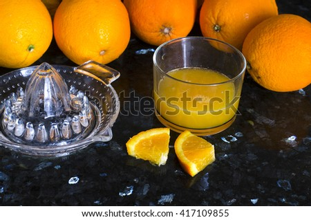 Citrus press with oranges and juice in glass on black background   - stock photo