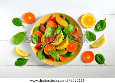 Citrus salad with fresh spinach leaves, healthy vitamin boost for breakfast - stock photo