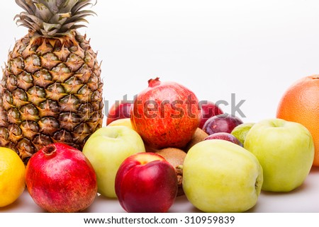 Citrus tropical colorful fruits of pineapple orange juicy grapefruit yellow lemon ripe nectarine purple plum red pomegranate kiwi lime and green apple on white background copyspace, horizontal picture - stock photo