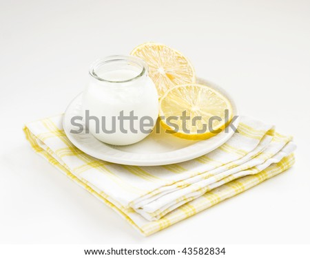 Citrus yogurt and fresh lemons on white