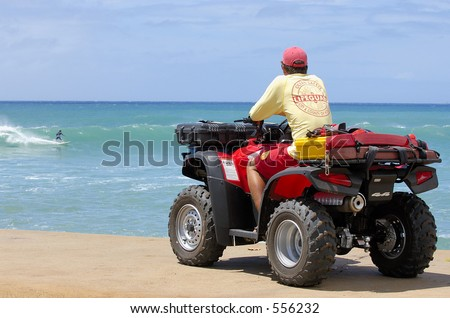City and Couty of Honolulu Lifeguard watches over surfers at Ala Moana Beach Park in Hawaii. - stock photo