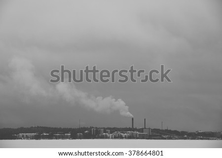 City and the smoke. An image of a cityscape taken from far away with some smoke coming from chimney. Image taken on a very cloudy day. Image has some noise added and vintage effect.
