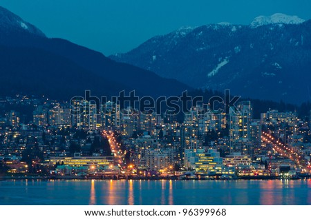 City at night, panoramic scene reflected in water, North Vancouver, Canada. - stock photo
