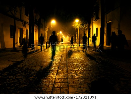 City at night. Shadows of people walking down the street - stock photo