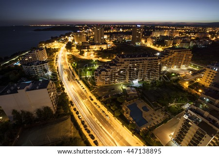 City at the bank of the ocean with buildings and hotels during sunset. View from above. Portimao, Algarve, Portugal. - stock photo