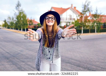 City autumn fashion lifestyle portrait of young sensual blonde woman, wearing trendy white jeans, hipster glasses and hat, posing at countryside, having fun alone, soft film colors. - stock photo