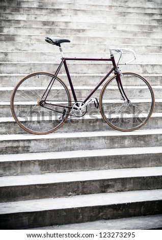 City bicycle fixed gear and concrete wall. Classic vintage style road bike on gray stairs. Stylish retro bike and gray industrial building. - stock photo