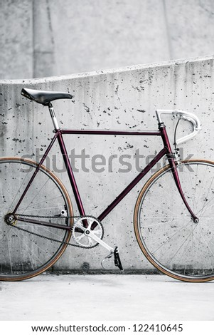 City bicycle fixed gear and concrete wall. Vintage style bike and gray industrial building - stock photo