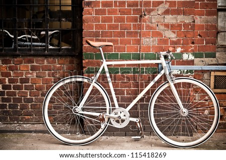 City bicycle fixed gear and red brick wall, vintage bike. Retro stylish cycling in town, old retro bike, cycling or commuting in city urban environment, ecological transportation concept - stock photo