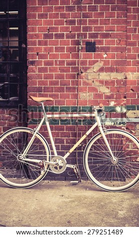 City bicycle fixed gear and red brick wall, vintage bike. Retro stylish cycling in town, old retro fix cycle, cycling or commuting in city urban environment, ecological transportation concept