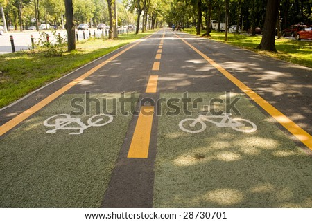 City bike lane along shady wooden street - stock photo