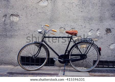 City bike over gray wall. Europe. - stock photo