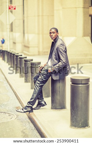 City Boy. Wearing fashionable jacket, pants, leather shoes, wristwatch, a hand in pocket, young black teenage boy is sitting on street, looking up, wondering. Street Fashion. Retro filtered look. - stock photo