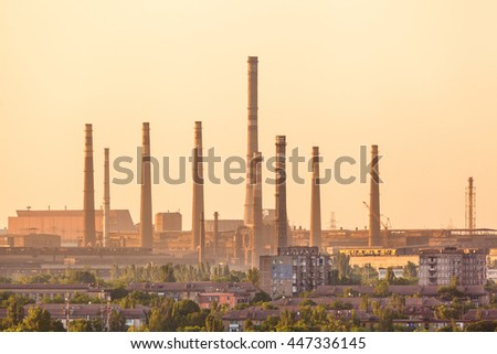 City buildings on the background of steel factory with smokestacks at colorful sunset. metallurgical plant. steelworks, iron works. Heavy industry. Air pollution from smokestacks. Industrial landscape - stock photo