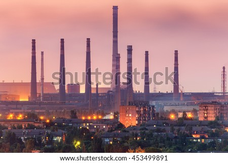 City buildings on the background of steel factory with smokestacks at night.  Metallurgical plant with chimney. steelworks, iron works. Heavy industry. Air pollution, smog. Industrial landscape - stock photo
