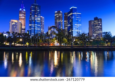 city buildings reflected in river - stock photo