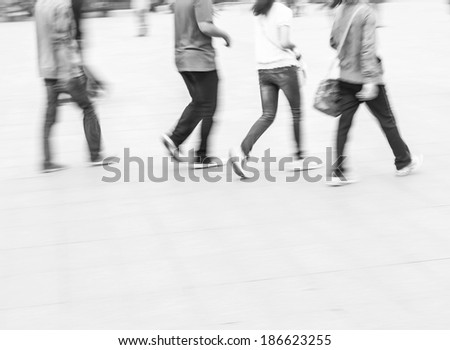 City business people walking in railway station square, black and white blur background - stock photo