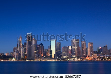 city cbd sunrise blue sky tall skyscrapers business district illuminated office windows harbour view reflection - stock photo