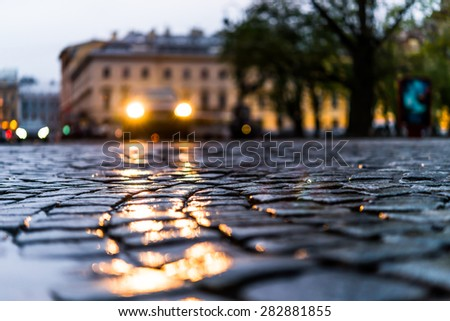 City central square paved with stone after a rain, headlights from car in the distance. View from the pavement level - stock photo