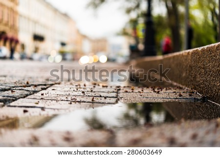 City central square paved with stone after a rain, headlights from cars in the distance. View from the pavement level next to the roadside puddle - stock photo