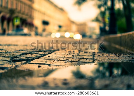 City central square paved with stone after a rain, headlights from cars in the distance. View from the pavement level next to the roadside puddle, image in the orange-blue toning - stock photo