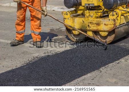 City crew install a new speed bump for slowing traffic near school. Selective focus. - stock photo