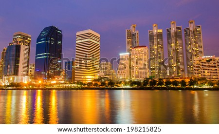 city downtown at night with building reflection in the river Bangkok, Thailand - stock photo