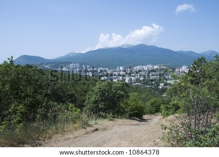 City in the Crimean mountains with road in the foreground - stock photo