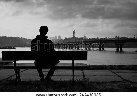 City landscape, abstraction. Young man sitting on a bench near the river. On the opposite bank panormama city: churches, houses, trees. Right Bridge. Kiev. Ukraine. Dnepr. The outline shooting. - stock photo