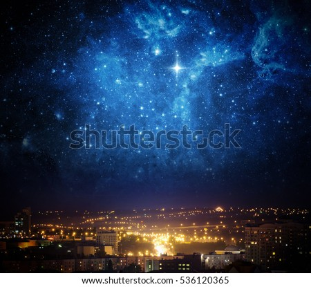 City landscape at nigh with sky filled with stars. Elements of this image furnished by NASA