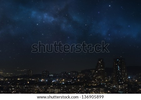 City landscape at nigh with sky filled with stars, nebula and galaxy - stock photo