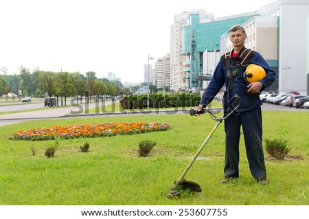 City landscaper gardener with gas trimmer on green grass - stock photo