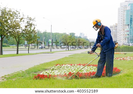 City landscaper man gardener cutting grass around planted flowers with string lawn trimmer - stock photo