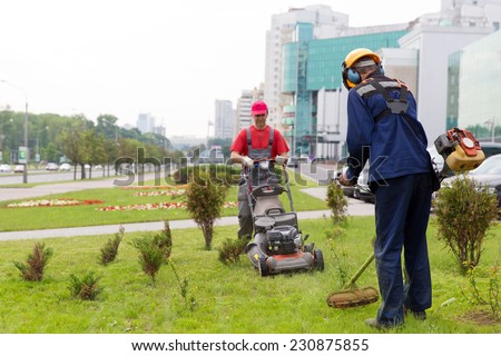City landscapers gardeners mowing lawn with gas trimmer and lawnmower machine - stock photo