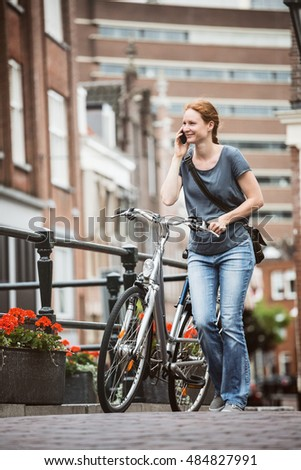 City life - a young woman talking on the phone and pushing a bicycle on a street in a European town.