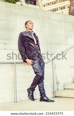 City Life. Wearing a fashionable jacket, pants, leather shoes, a young black college student standing against the wall, sad, thinking. Concept of teenager self esteem. Retro filtered look.  - stock photo