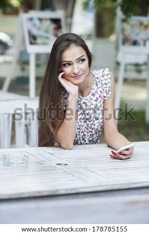 City lifestyle business woman using smartphone on cafe outdoor. Young professional female businesswoman on smart phone while sitting indoors in cafe looking out. beautiful and sexy - stock photo