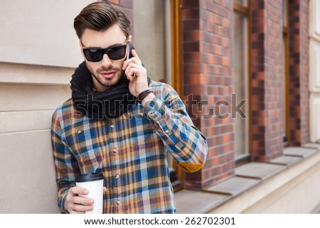 City lifestyle. Handsome young man holding coffee cup and talking on the mobile phone while standing at the street  - stock photo