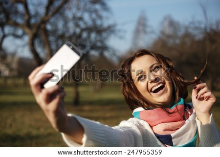 City lifestyle stylish hipster girl using a smartphone taking photo selfie with camera in a park - stock photo
