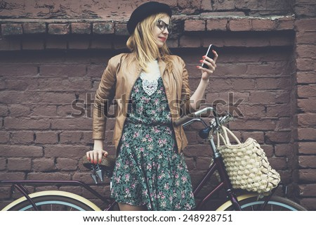 City lifestyle stylish hipster girl with bike using a phone texting on smartphone app in a street - stock photo