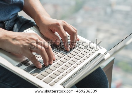 City lifestyle woman hand busy working on home office computer screen typing laptop keyboard using wifi cyber internet online digital media technology pc device in urban rooftop view environment - stock photo
